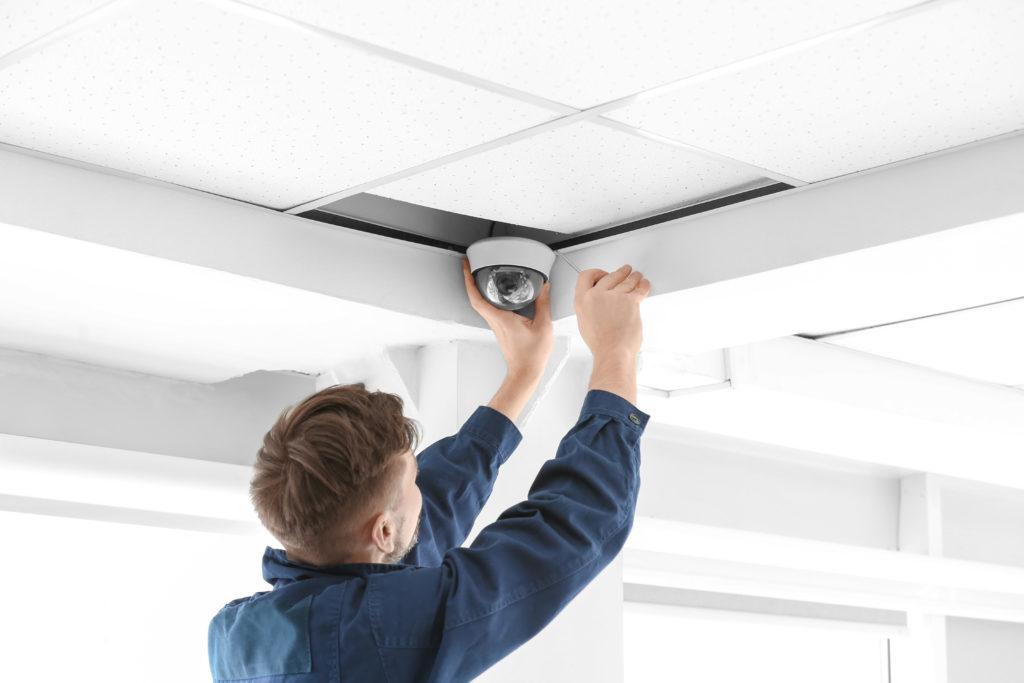 Technician installing CCTV camera on ceiling indoors
